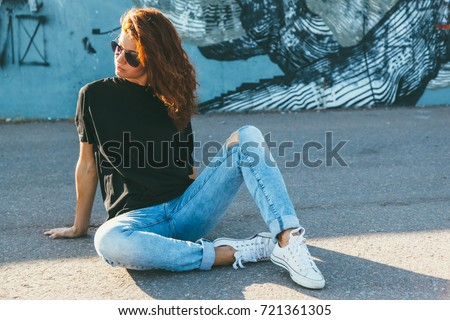 Model wearing plain black t-shirt, boyfriend jeans, sneakers and hipster sunglasses posing against street wall, teen urban clothing style, mockup for tshirt print store #721361305