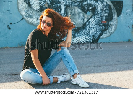 Model wearing plain black t-shirt, boyfriend jeans, sneakers and hipster sunglasses posing against street wall, teen urban clothing style, mockup for tshirt print store #721361317