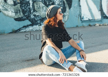 Model wearing plain black t-shirt, boyfriend jeans, sneakers and hipster sunglasses posing against street wall, teen urban clothing style, mockup for tshirt print store #721361326