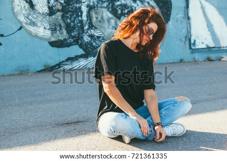 Model wearing plain black t-shirt, boyfriend jeans, sneakers and hipster sunglasses posing against street wall, teen urban clothing style, mockup for tshirt print store #721361335
