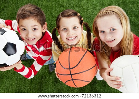 Image of happy friends on the grass with balls looking at camera Royalty-Free Stock Photo #72136312