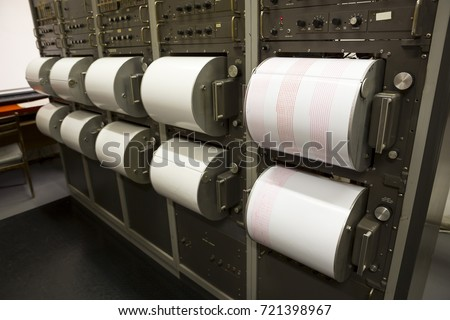 Seismograph records an earthquake on the sheet of measuring paper. Seismological device for measuring earthquakes. Seismograph machine needle drawing a red line on graph paper measuring activity. #721398967