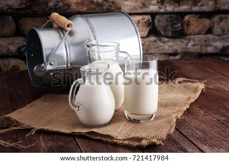 A jug of milk and glass of milk on a wooden table Royalty-Free Stock Photo #721417984