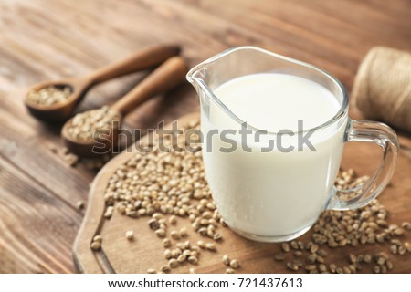 Jug with healthy hemp milk on wooden board #721437613