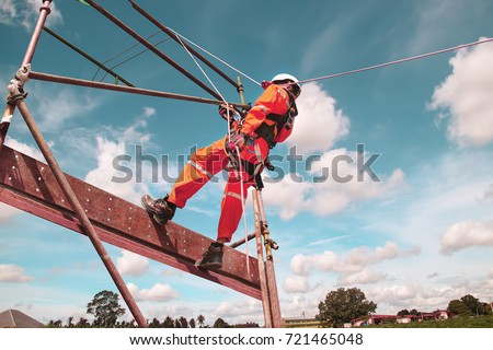 workers up high with safety equipment and safety belts, construction workers wearing safety harness belt high place on monotone. #721465048