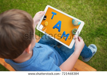 Child uses a tablet to learn letters. A creative app for playing and developing children ability.