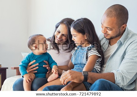 Multiethnic family playing with happy baby son at home. Parent and children relaxing together on the sofa at home in the living room. Little girl sitting on leg of dad looking her new cute brother. #721479892
