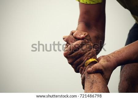 Mud race runners.Couple hold hands,help when overcoming hindrances mud #721486798