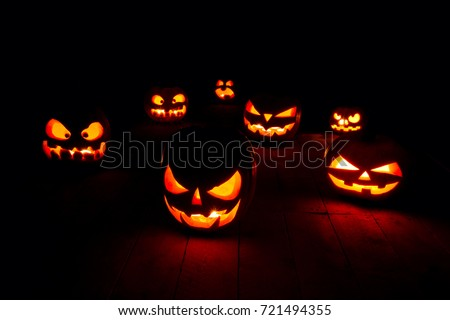 The concept of Halloween. Many glowing fiery light angry scary pumpkins. jack lantern in the dark, on a wooden background #721494355