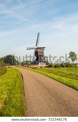 Dutch country road with a wooden hollow post polder mill from 1762, restored in 1953. The mill is now a national monument and no longer in use as a polder mill. #721548178