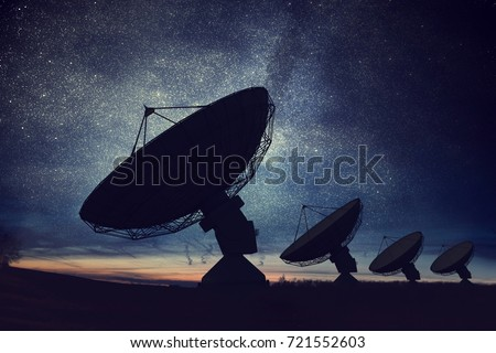 Silhouettes of satellite dishes or radio antennas against night sky. Space observatory. Royalty-Free Stock Photo #721552603