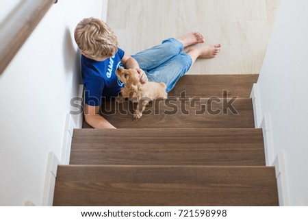 8 years old boy sitting on stairs with a cocker spaniel puppy #721598998