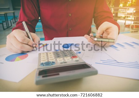 hand working writing and using smart phone with business strategy diagram report, calculator on desk at home office, income and expenses, finance, searching data, money cost savings, economy concept #721606882