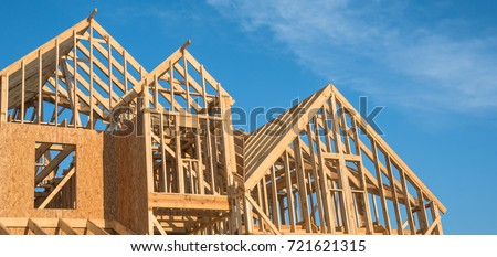 Close-up of gables roof on stick built home under construction and blue sky in Humble, Texas, USA. New build roof with wooden truss, post and beam framework. Timber frame house, real estate. Panorama #721621315