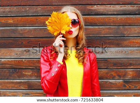 pretty woman with autumn yellow maple leaves over wooden background #721633804