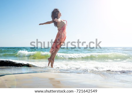 Happy young woman jumping on the beach #721642549