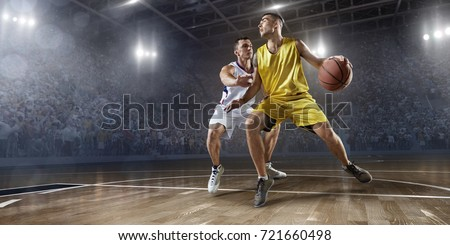 Basketball players on big professional arena during the game. Players fight for the ball. Players wearing unbranded clothes. #721660498