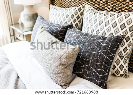 Closeup of new bed comforter with decorative pillows, headboard in bedroom in staging model home, house or apartment #721683988