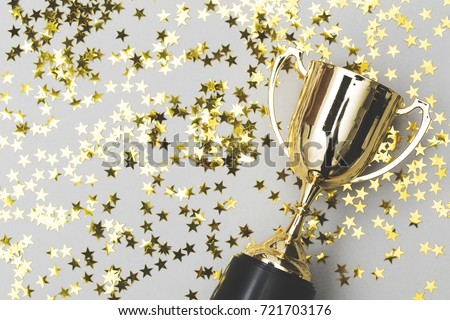 Gold winners trophy with golden shiny stars Royalty-Free Stock Photo #721703176