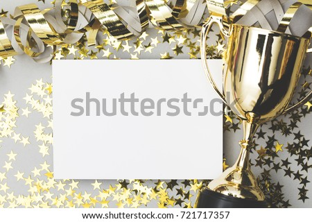 Gold winners trophy with a blank poster label and golden shiny stars Royalty-Free Stock Photo #721717357