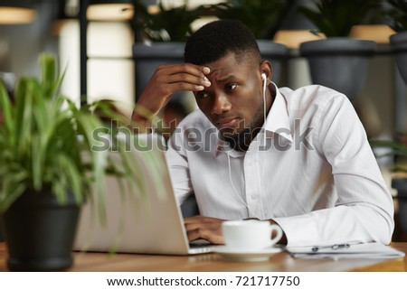 View of young african businessman looking at laptop, thinking, decided problem, have a stress. Handsome, stylish student, learning, working at cafe, listening music. Freelancer job. Loft interior. #721717750