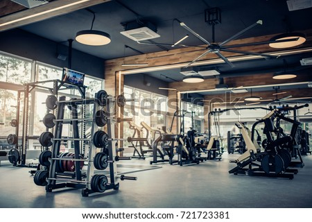 Modern light gym. Sports equipment in gym. Barbells of different weight on rack. Royalty-Free Stock Photo #721723381