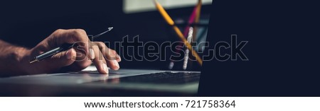 A man using laptop computer working on new project idea at his desk in the office late at night - panoramic web banner with copy space on the right #721758364