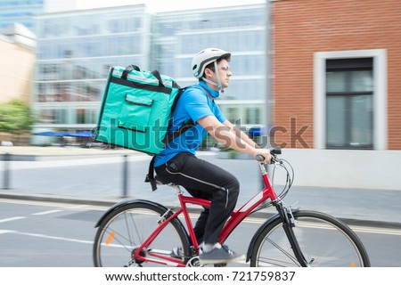 Courier On Bicycle Delivering Food In City #721759837