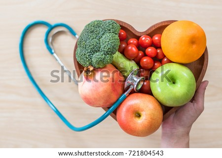 Cholesterol diet, diabetes control and healthy food nutritional eating for cardiovascular disease risk reduction concept with clean fruits in heart dish with nutritionist monitoring conceptual idea #721804543