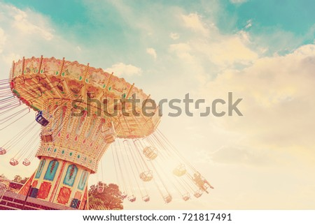 carousel ride spins fast in the air at sunset - vintage filter effects - a swinging carousel fair ride in amusement park at dusk Royalty-Free Stock Photo #721817491