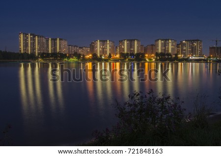 Residential complex of skyscrapers and the waterfront across the river reflected in the water. Night cityscape #721848163