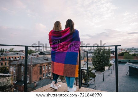 Couple young girls staying on city background. Spending good time together on roof, unusual places for rest and entertainment, open space leisure and best friends forever concept. Free space