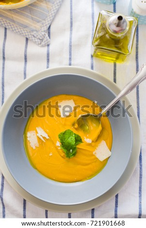 Top view of a dish of Pumpkin soup with coconut cream
