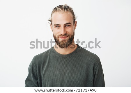 Portrait of beautiful mature blonde bearded guy with trendy hairdo in casual grey shirt smiling and looking in camera. Royalty-Free Stock Photo #721917490