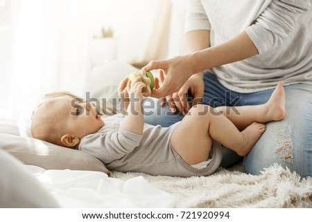 Little baby boy spending happy childhood with young mother. Child trying to take a beautiful toy from tender mom hands. Family concept. #721920994