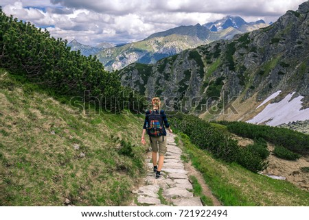 GIrl with backpack trekking on the rocky path in Tatra mountains, Poland #721922494