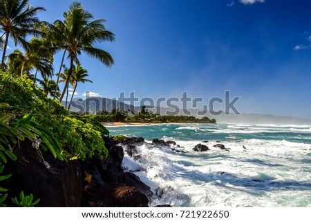 Waves crashing on rocks at Oahu's north shore coast (Turtle Beach) near the town of Haleiwa. Spray in the air; the mountain range in the background marks the western tip of Oahu, Ka'Ena Point. Hawaii. Royalty-Free Stock Photo #721922650