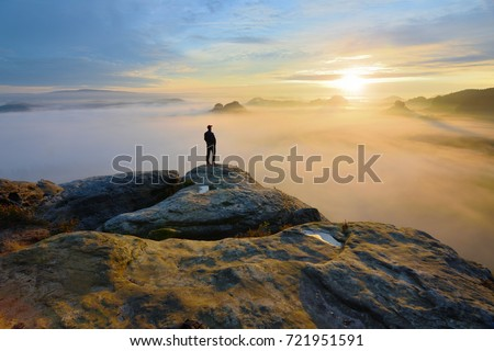 Hiker on rock end above valley. Man watch over misty and autumnal morning valley to bright morning Sun. Tourist  looking to misty valley bellow. Autumn cold weather #721951591