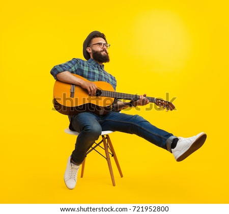 Handsome hipster musician man sitting and playing guitar.  Royalty-Free Stock Photo #721952800