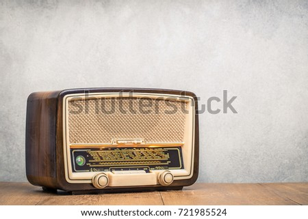 Retro broadcast radio receiver with green eye light on wooden table circa 1950 front concrete wall background. Listen music concept. Vintage instagram old style filtered photo #721985524
