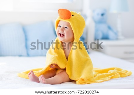 Happy laughing baby wearing yellow hooded duck towel sitting on parents bed after bath or shower. Clean dry child in bedroom. Bathing and washing of little kids. Children hygiene. Textile for infants. #722010274