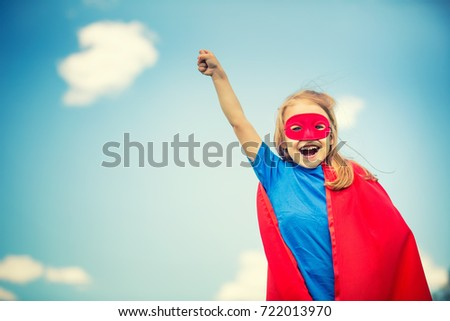 Funny little girl playing power super hero over blue sky background.  #722013970