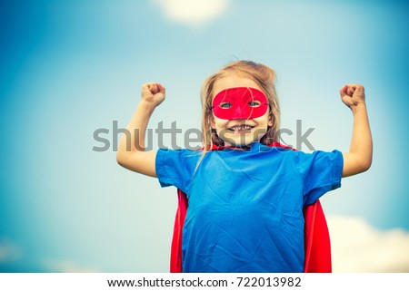 Funny little girl playing power super hero over blue sky background. 3 #722013982