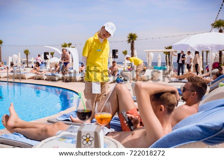 Odessa, Ukraine May 8, 2015: Men and woman relaxing in luxury beach resorts during summer holidays. boy and girl has rest on day lounge party at elite beach resorts of Ibiza. #722018272