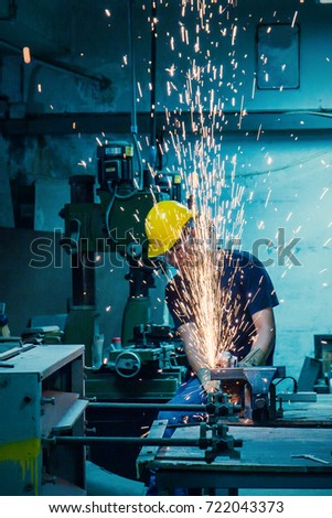 Heavy industry manual worker with grinder background, asian man wearing mask with his hands grinding in heavy industry Royalty-Free Stock Photo #722043373
