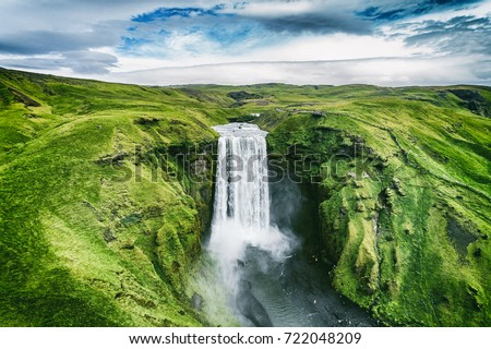 Iceland waterfall Skogafoss in Icelandic nature landscape. Famous tourist attractions and landmarks destination in Icelandic nature landscape on South Iceland. Aerial drone view of top waterfall. #722048209