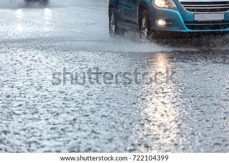 rainwater spraying from car wheels. city road during heavy rain. #722104399