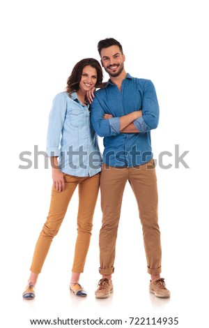 happy woman leaning on her man's shoulder; young casual couple smiling on white background, full body picture
