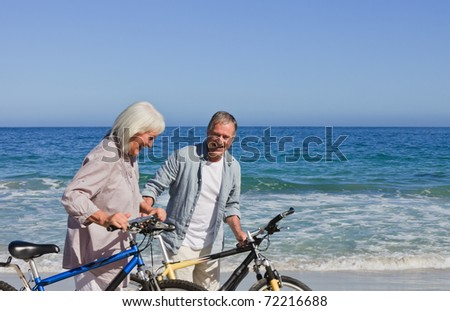 Retired couple with their bikes on the beach #72216688