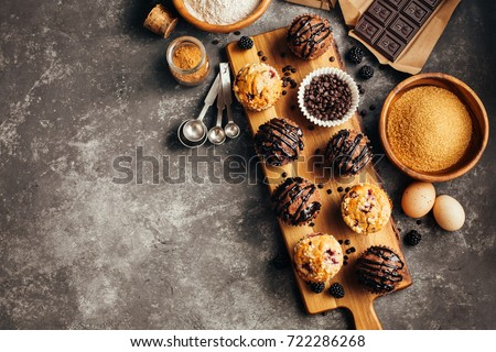 Different homemade muffins with chocolate and berries and baking ingredients. Food background wiht copyspace. Royalty-Free Stock Photo #722286268
